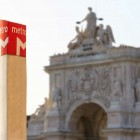 Metro sign at the commerce square in Lisbon, Portugal, with the gate in the background-1400