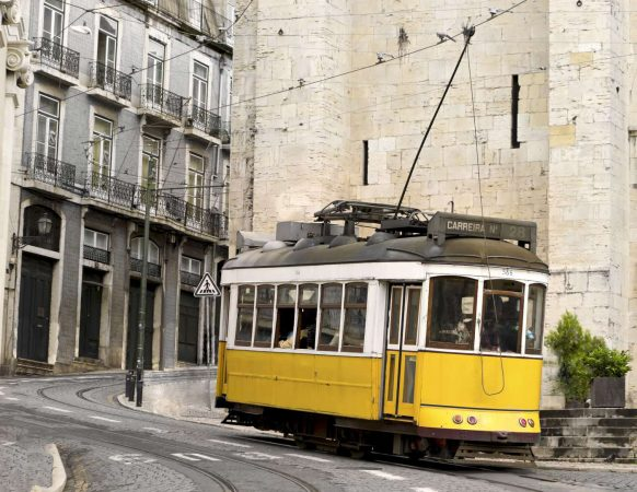 historic classic yellow tram of Lisbon built partially of wood navigating, narrow, winding streets, Portugal-1400