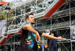 Unidentified young juggler with two crystal balls shows his art to the public near Pompidou Centre.-1600